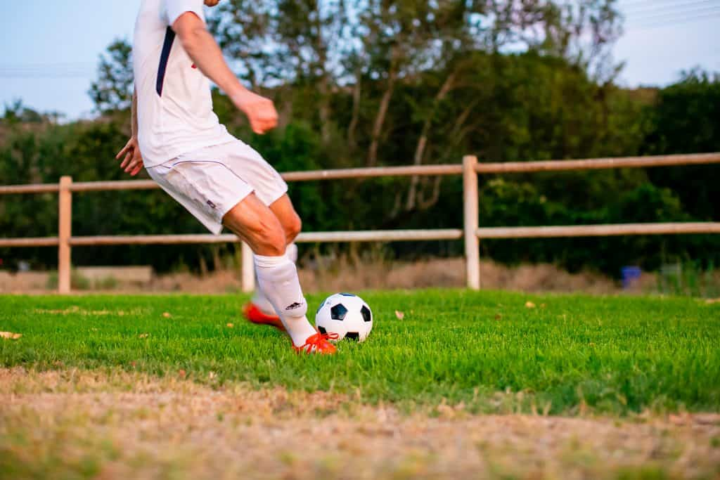 Man preparing to kick the soccer ball on the field