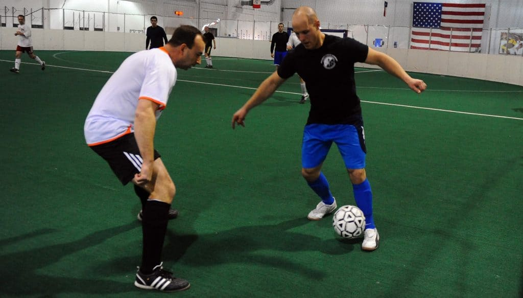 Two men playing with a white soccer ball on an indoor soccer field