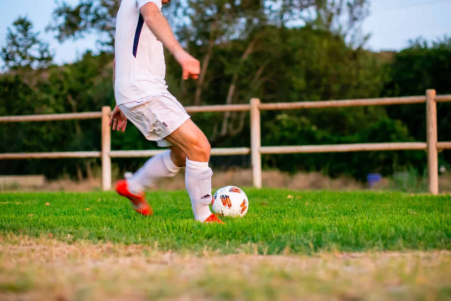 Man about to kick the soccer ball in the field
