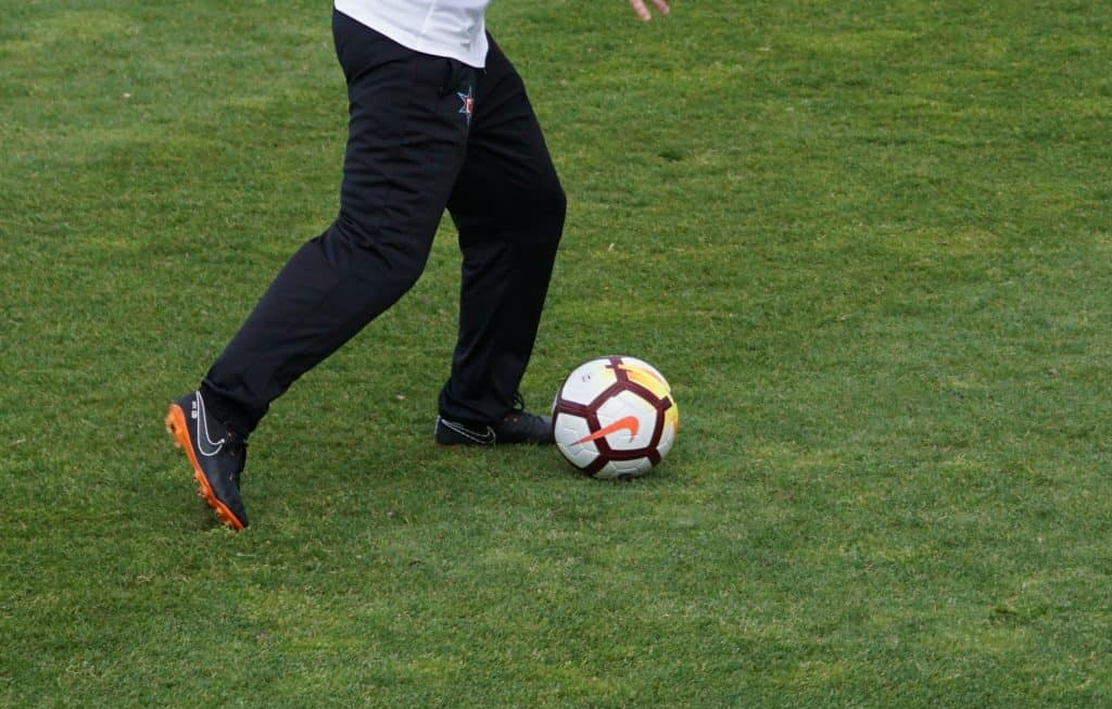A woman about to hit the soccer ball in a soccer field