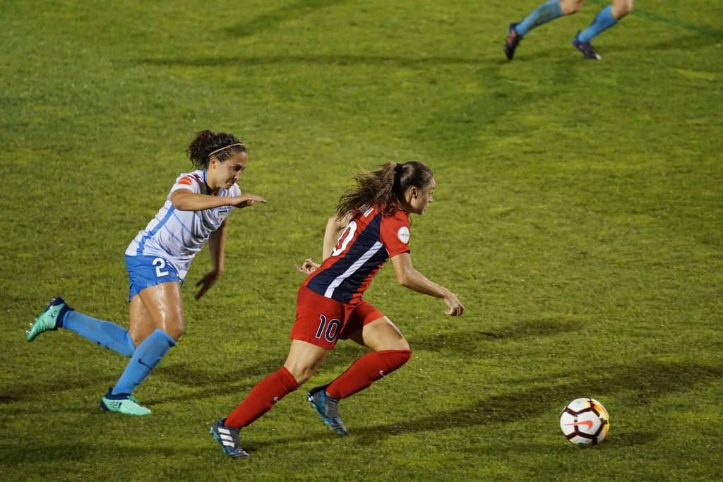 Two girls chasing after each other in soccer