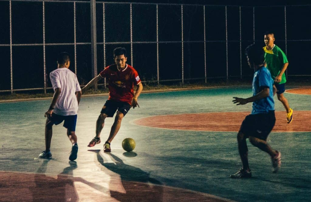 A man is about to make a through pass in a street style soccer match
