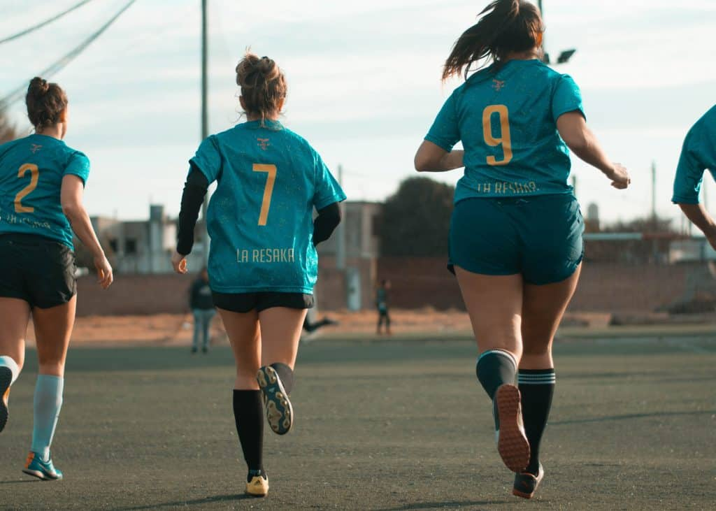 Group of women wearing the same jerse running away in the field