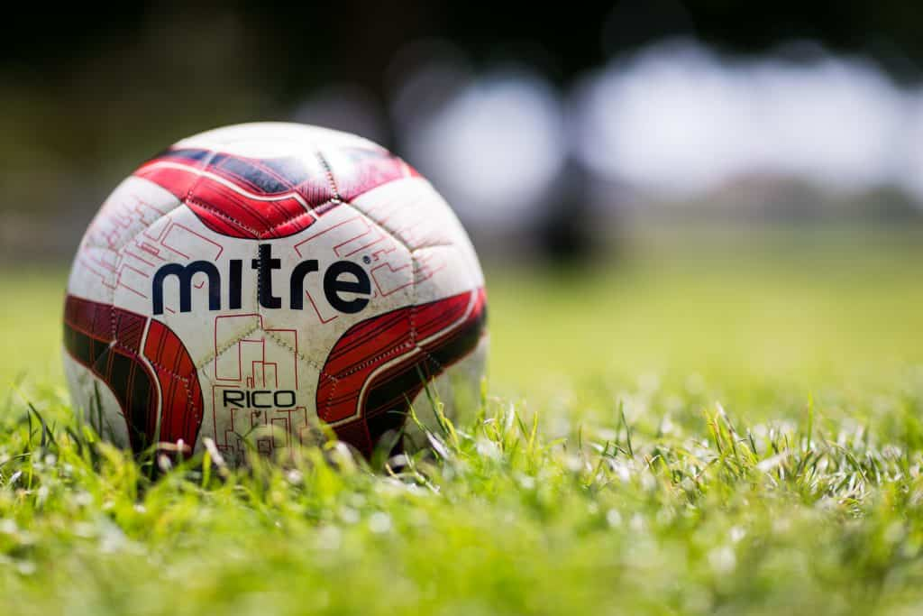 Close up of a mitre soccer ball in the middle of the grassy field