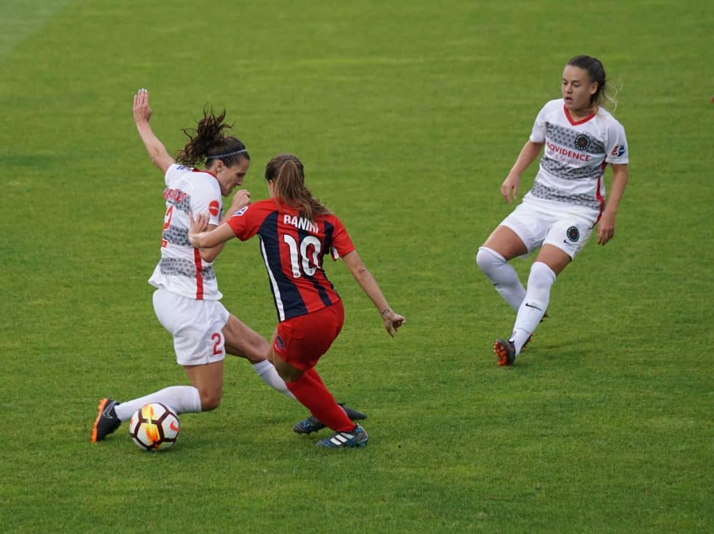 Soccer player in red tries to pass ball through defenders