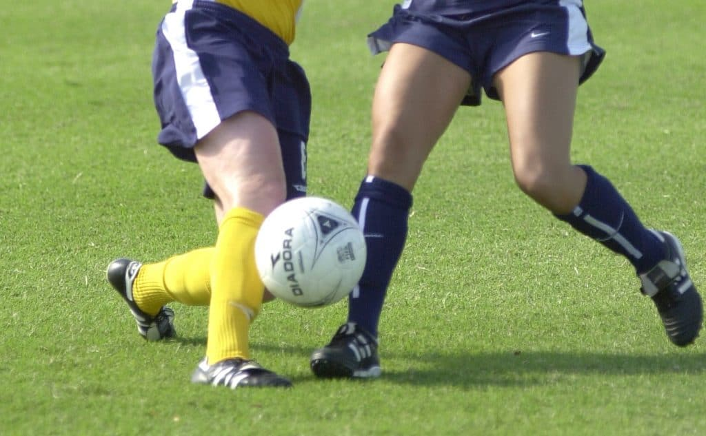 Two women fighting over the soccer ball