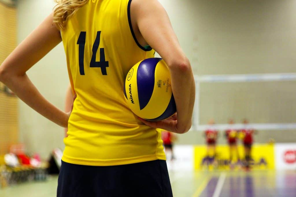 Woman with a yellow 14 jersey stands with a volleyball