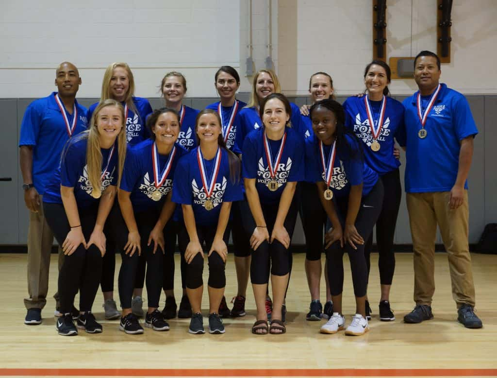 Team of volleyball girls in blue wearing a medal after winning