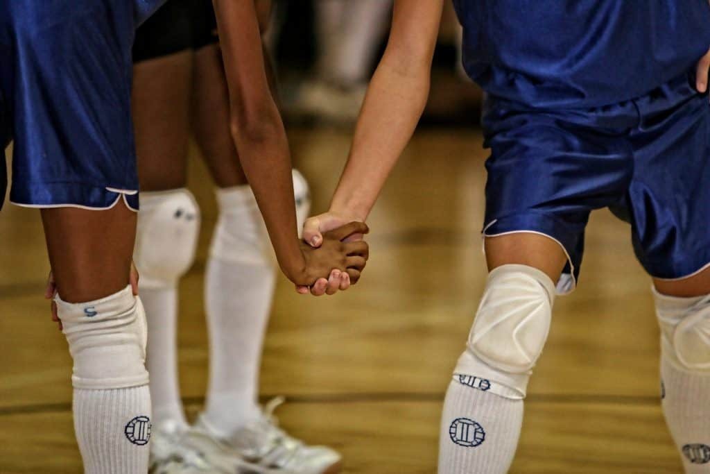 Two teammates hold hands in volleyball court