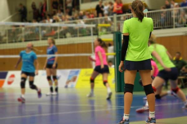 Woman in green stands before her teammates and enemies in a volleyball match