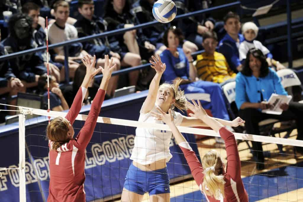 Volleyball ball player in white spikes to the other side of net