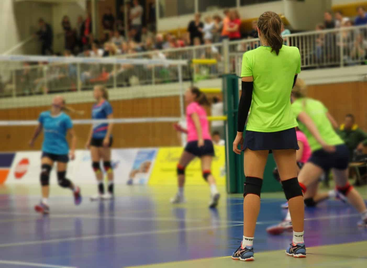Girl in green stands infront of a volleyball court during a match