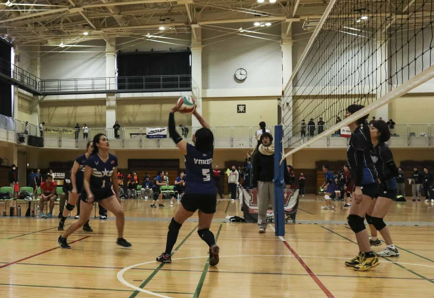 Setter passes volleyball to two teammates