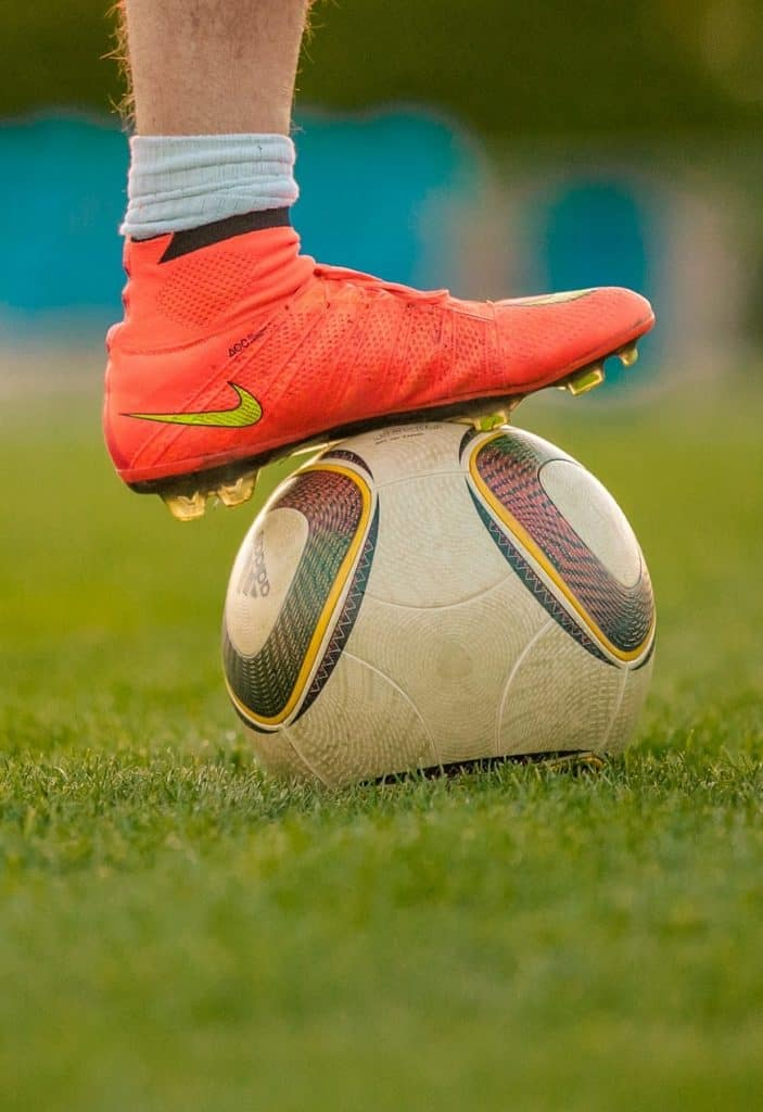 Nike soccer cleats stepping on a soccer ball