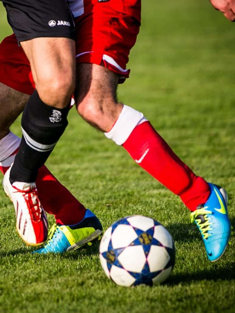 Two men trying to take the soccer ball using their feet