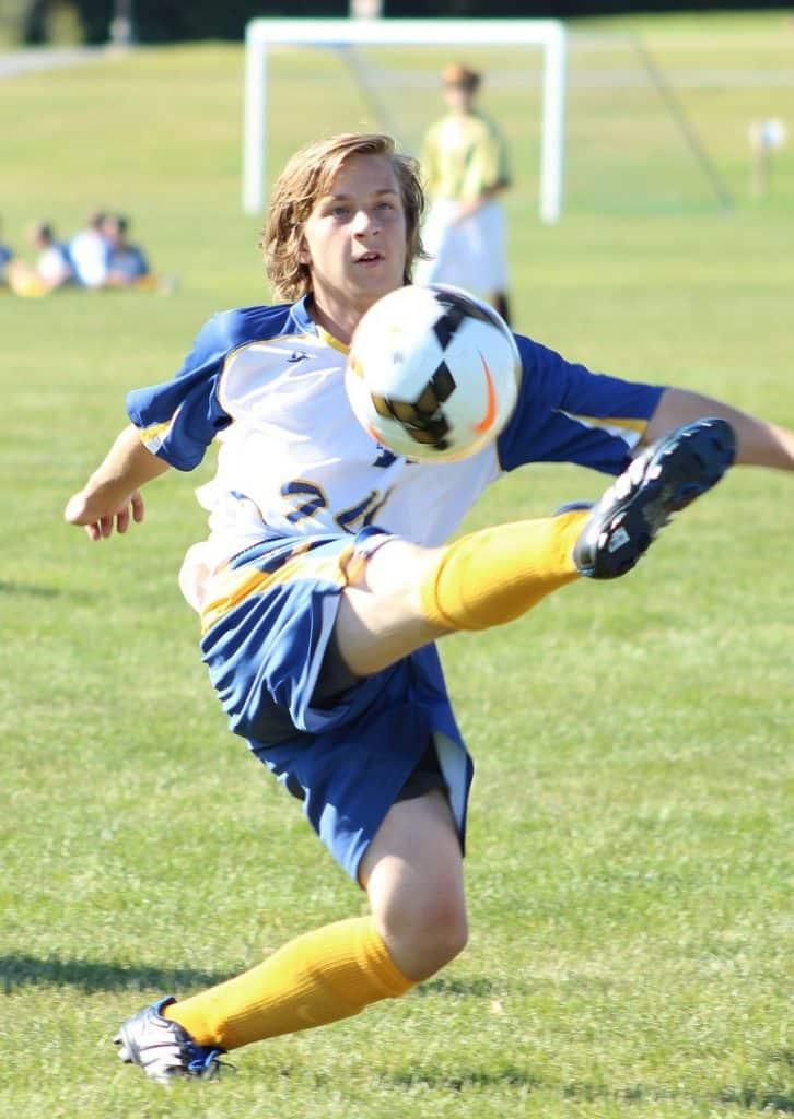 Man kicking a soccer ball in air