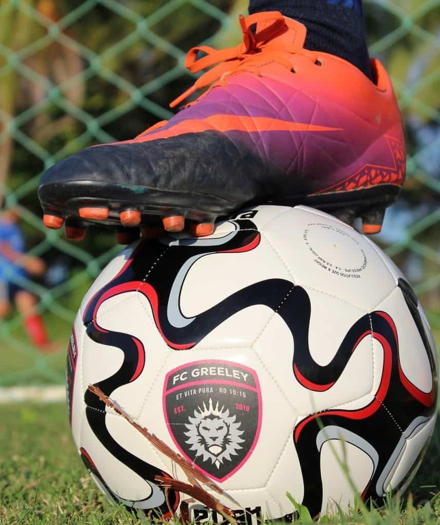Close up of an orange Nike soccer cleat on a soccer ball