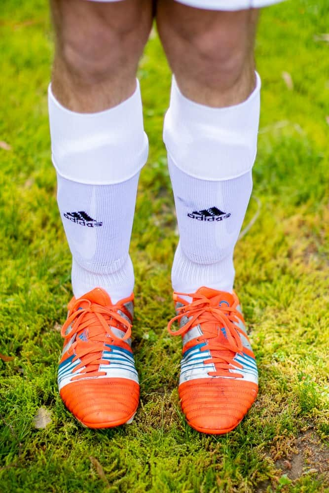 Man in white long socks and orange soccer cleats