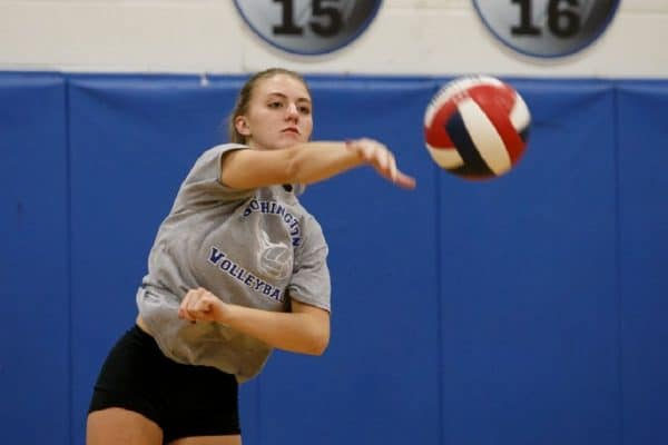 Girl wearing a gray shirt spiking a volleyball