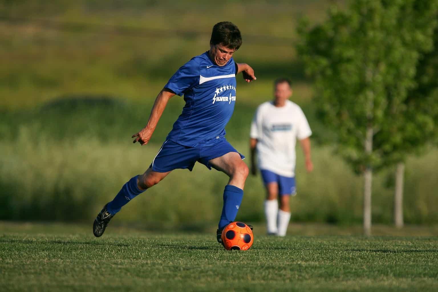Man in blue kicks the soccer ball