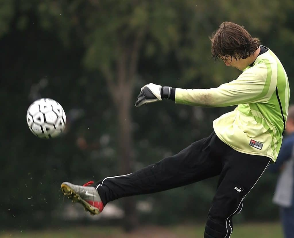 Soccer player throws a punt kick from the goal