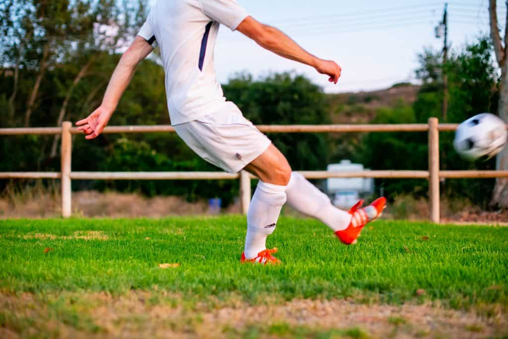 Man with his leg straight out after kicking the soccer ball
