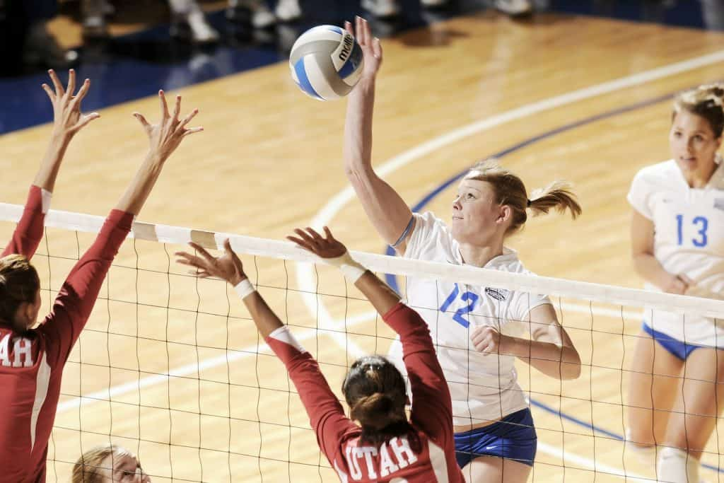 Volleyball player tries to make a spike while 2 other players are blocking