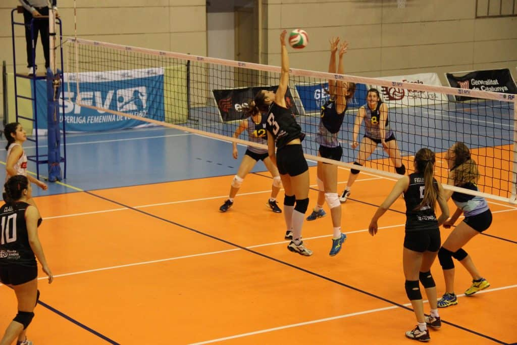 Volleyball players spiking and blocking over the net