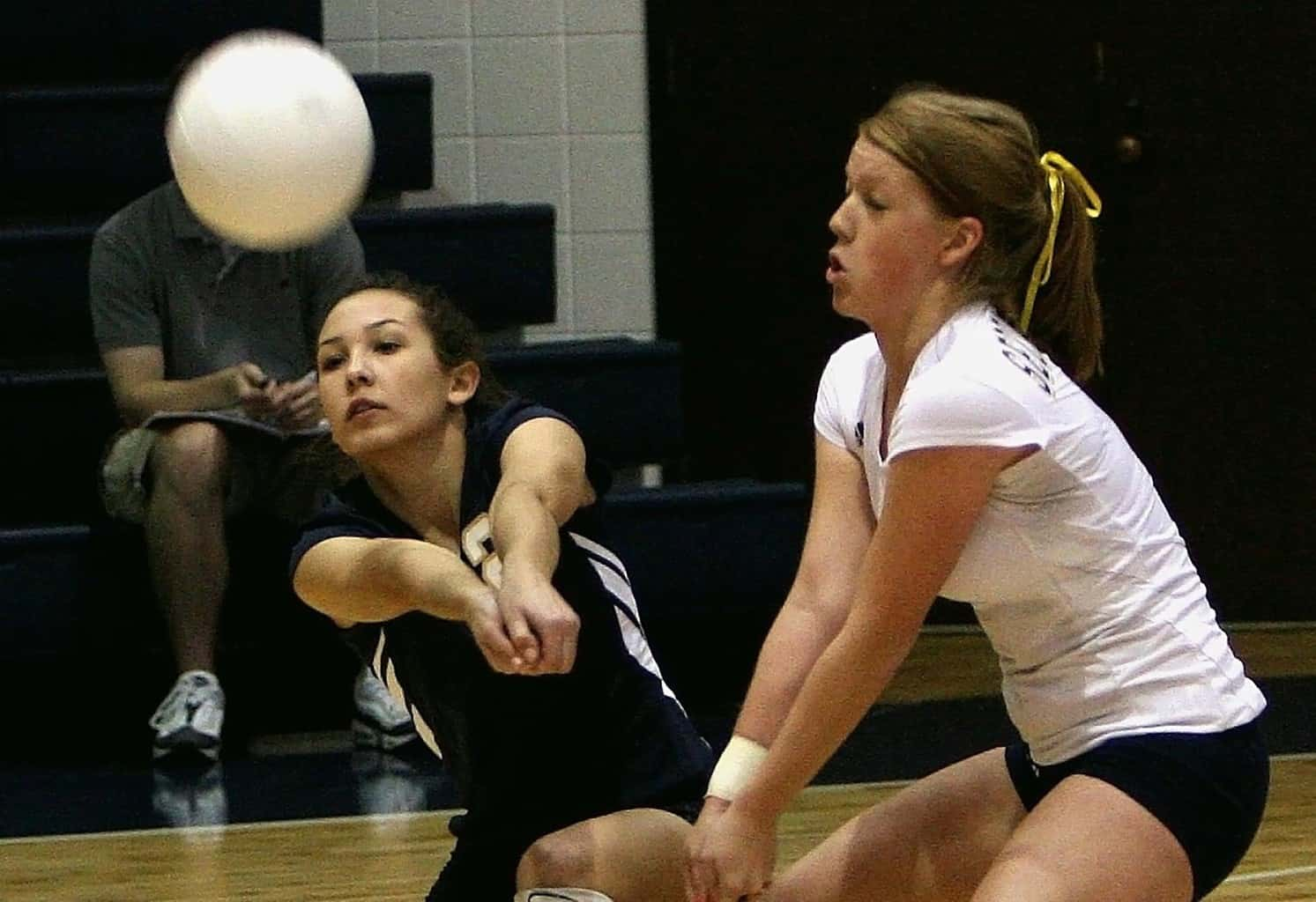 Two volleyball players receiving the ball
