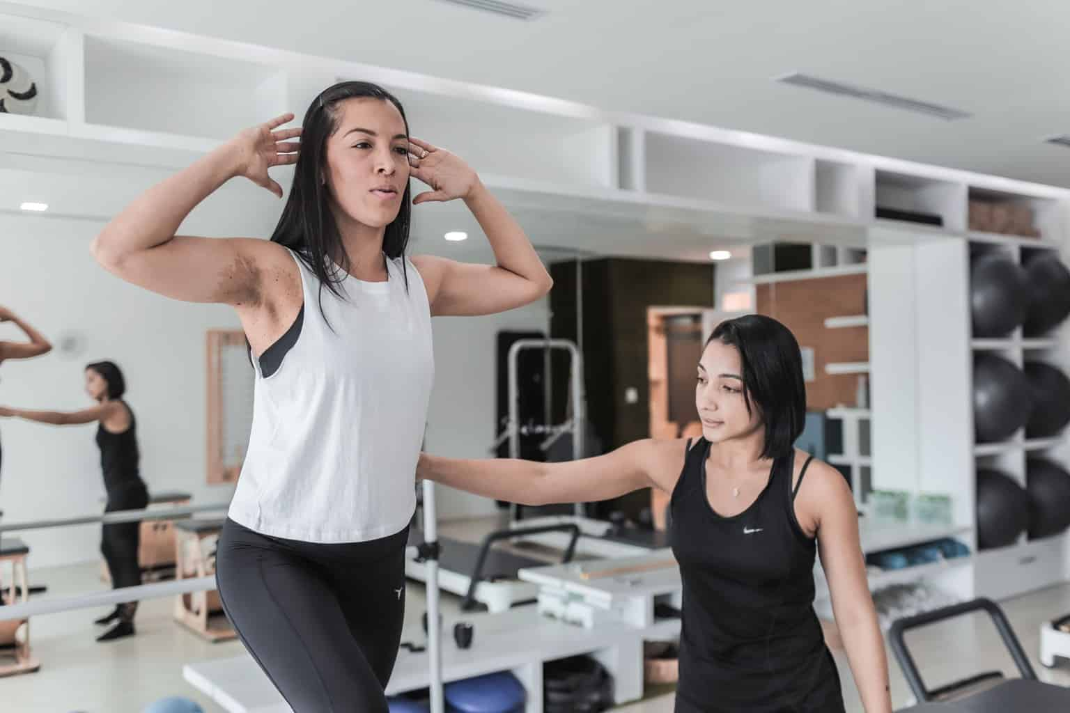 Two girls spotting each other while working out