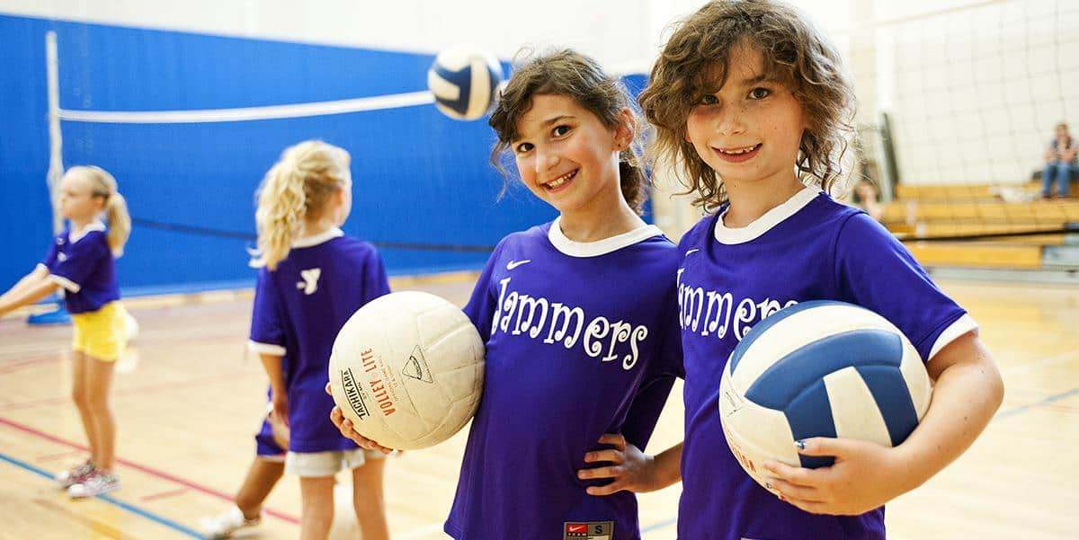 Volleyball players youth smiling while holding a volleyball