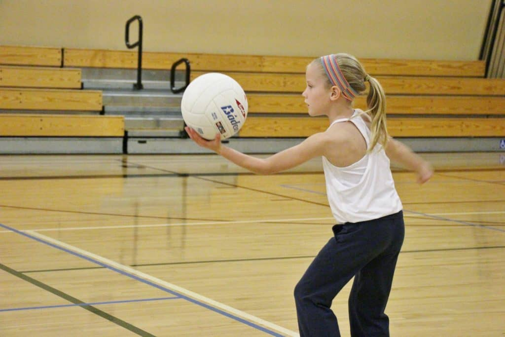 Little girl using volleyball to serve