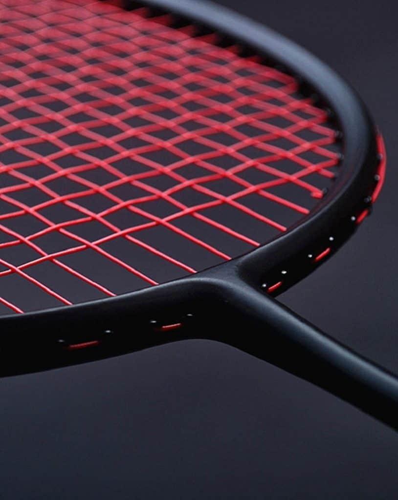 Black badminton racket with red strings