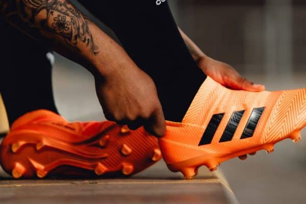 A man fitting an orange Adidas soccer cleat