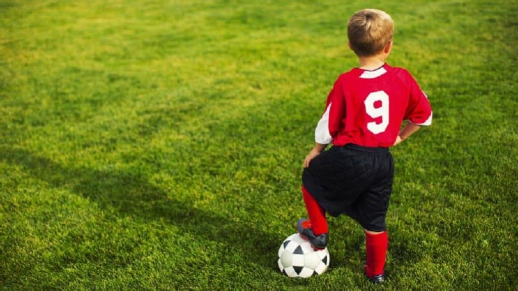 Young boy in red stepping on a soccer ball