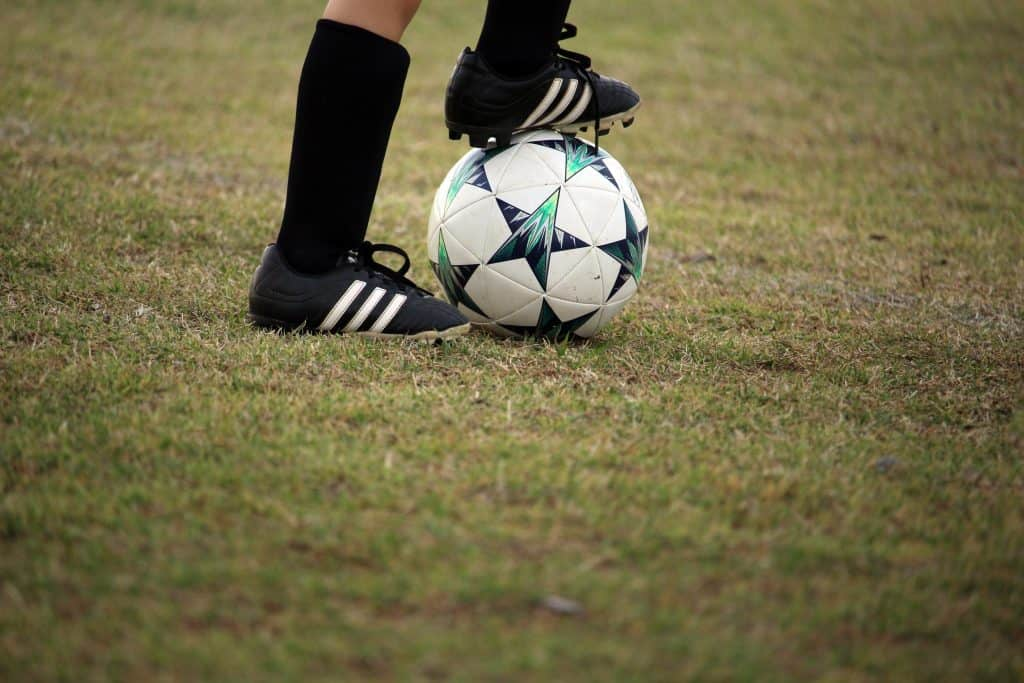 A kid stepping on a soccer ball on the field
