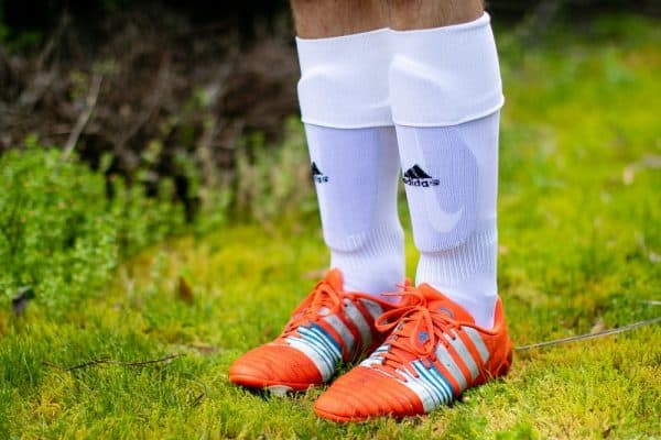 Close up of a man wearing white socks and orange soccer cleats
