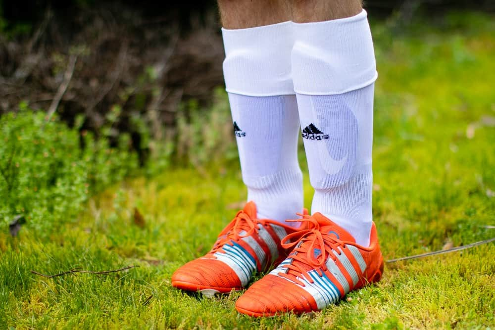 A boy wearing white socks and orange soccer cleats