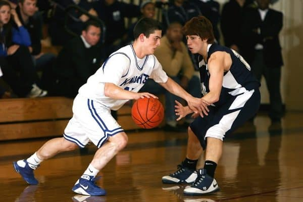 Basketball player dribbling the ball while running away from an opponent