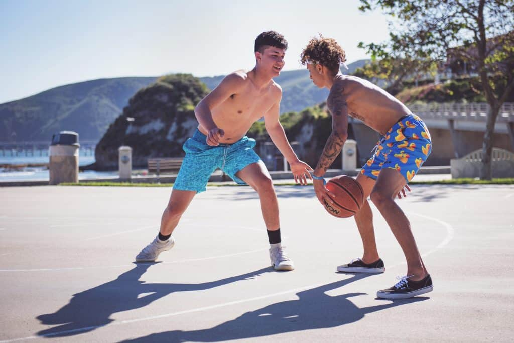 Two boys in an outdoor court playing basketball