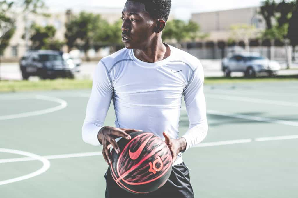 Man in white long sleeved dri fit top holds a basketball on the court