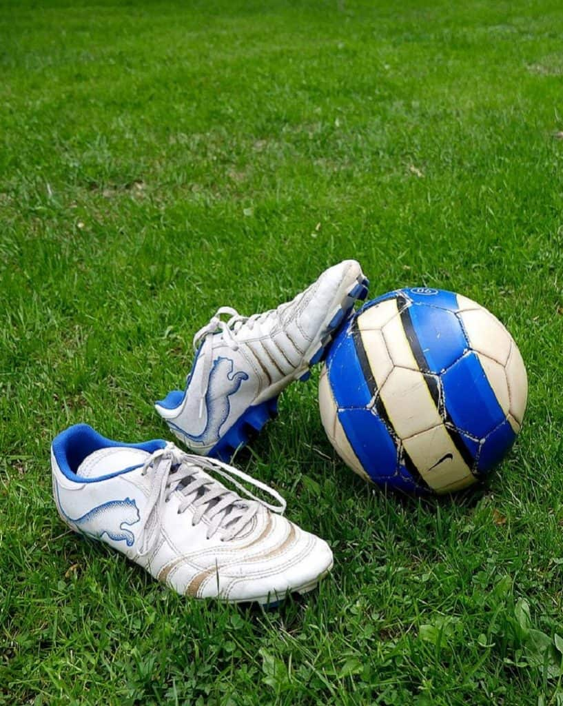Soccer cleats and a blue and white ball on a field