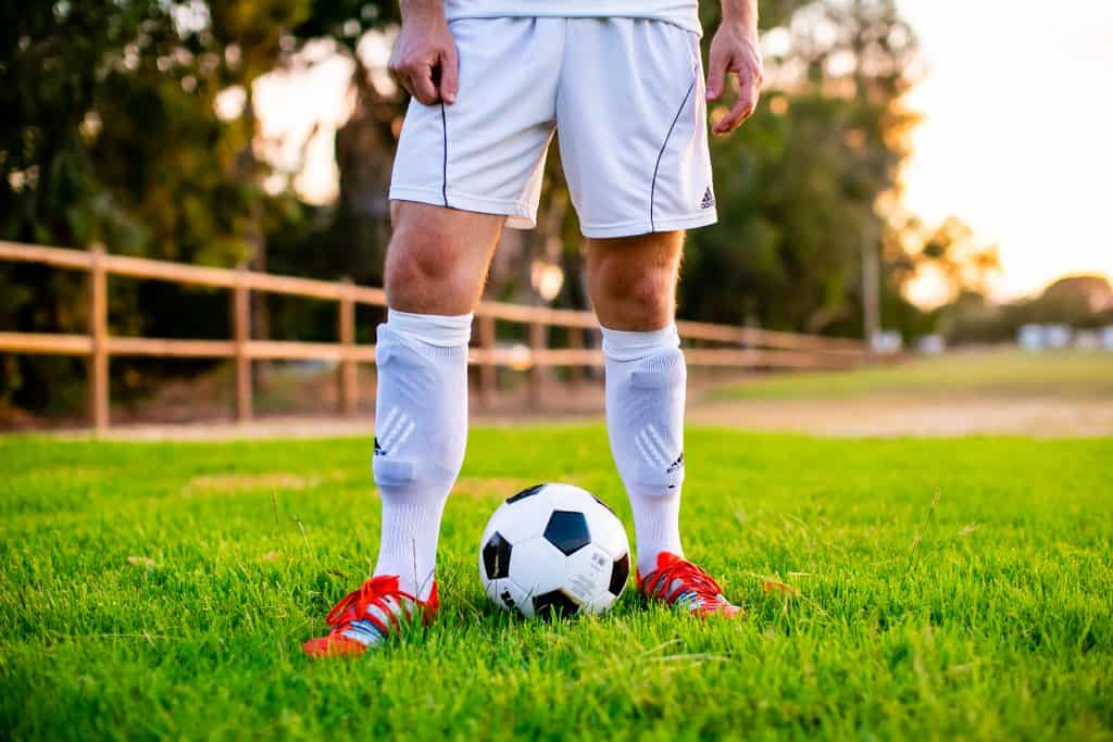 Man standing in soccer cleats, socks with a soccer ball
