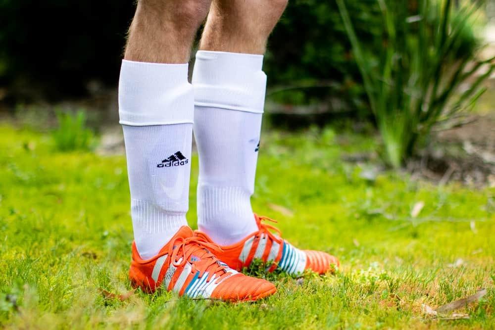 Man standing in orange soccer cleats and white soccer socks