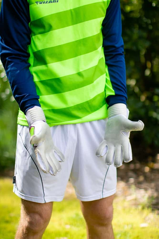 Man standing with white goalie gloves