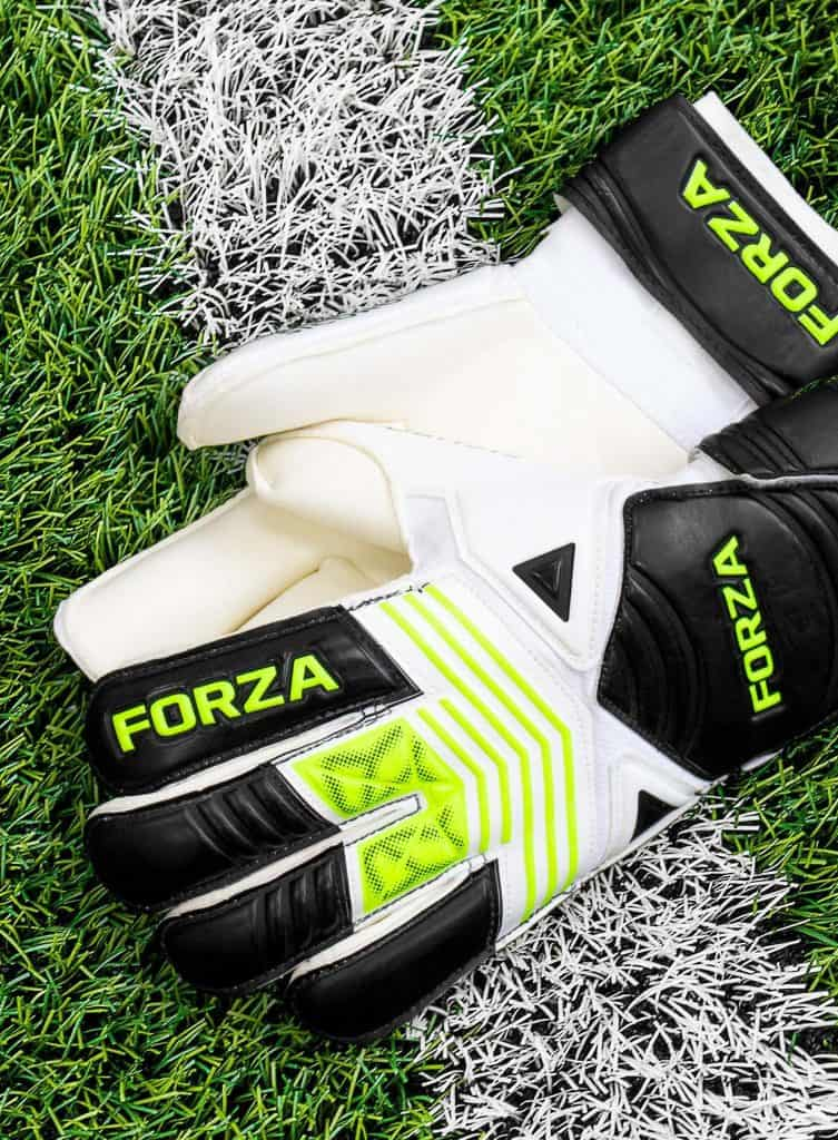 A pair of white goalkeeper gloves on the grass