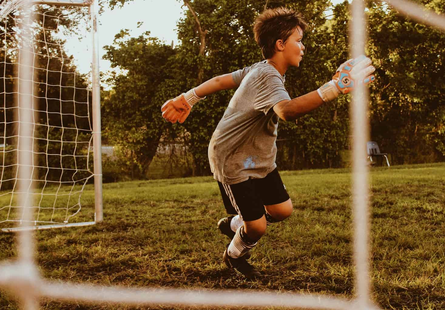 Young goalie kid running to protect the goal