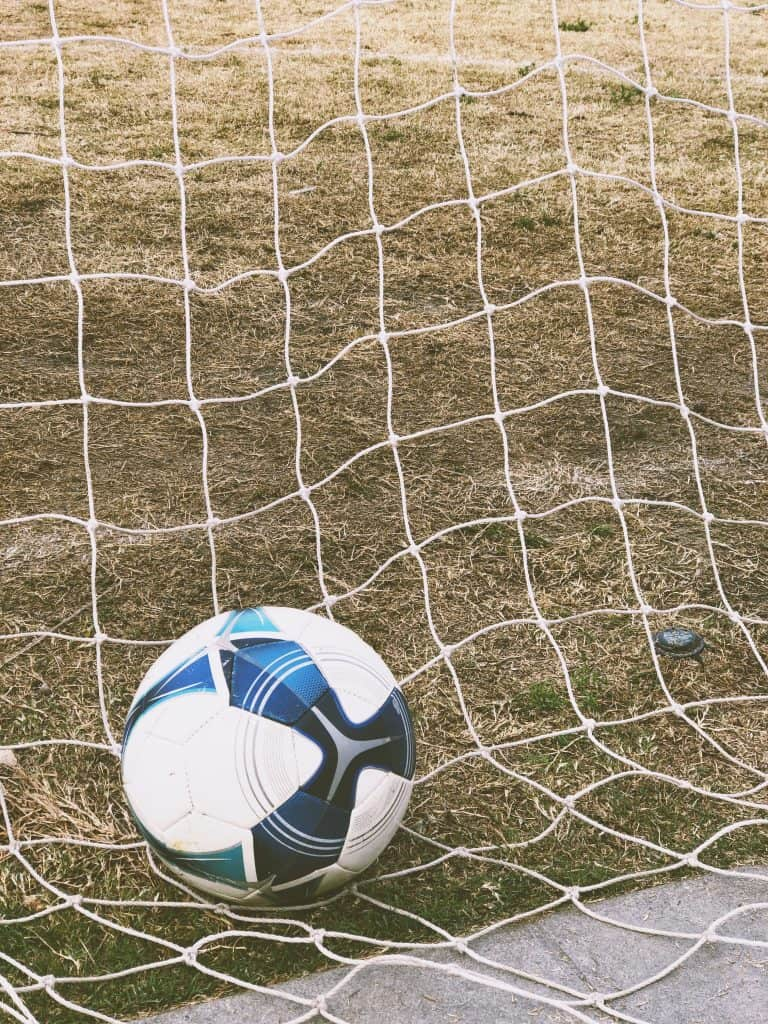 White and blue soccer ball in a net