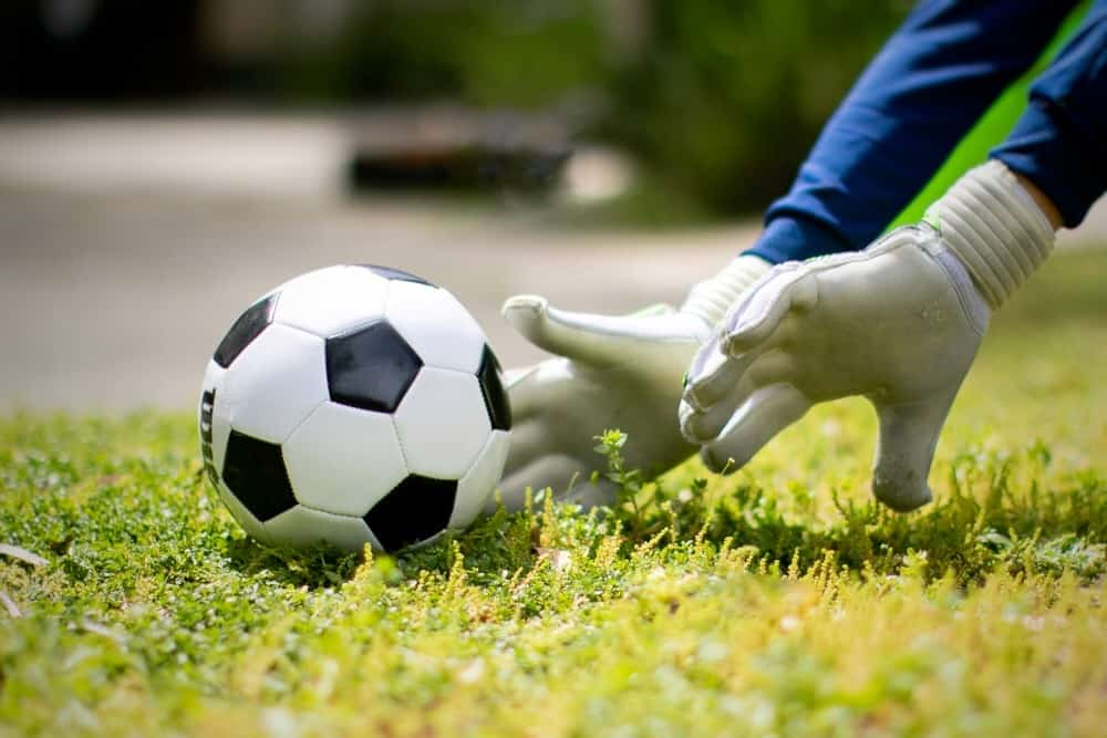 Man pushing the soccer ball on the grass