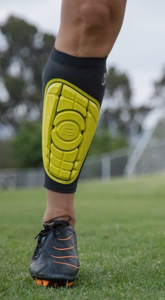 Man wearing yellow shin guards on the field